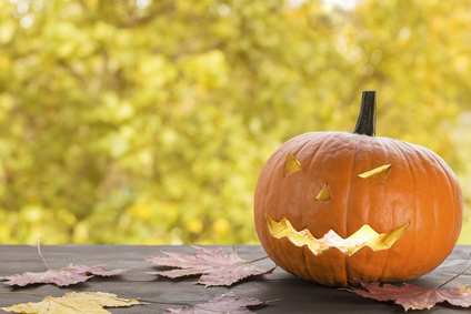 halloween pumpkin, jack-o-lantern on wooden table with autumn bokeh background. image with copy space